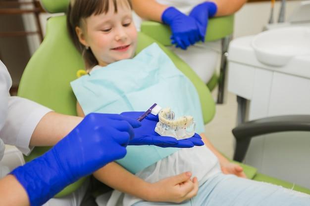 Dentista con dentaduras postizas con cepillo de dientes