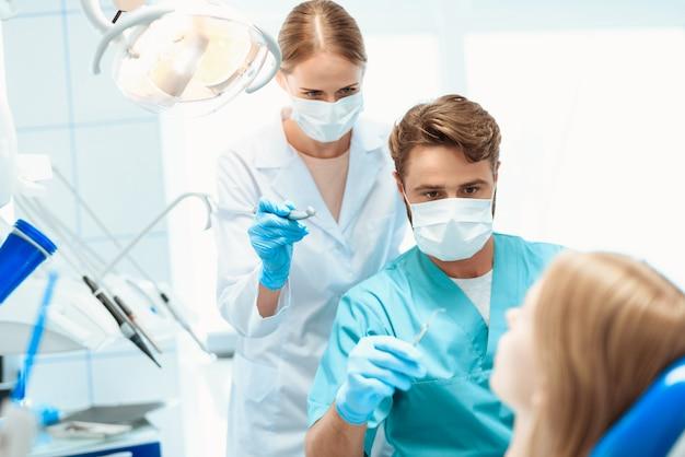 Un dentista y una enfermera están tratando al paciente.