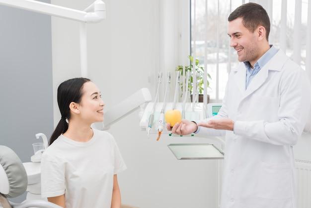 Dentista enseñando manzana a paciente