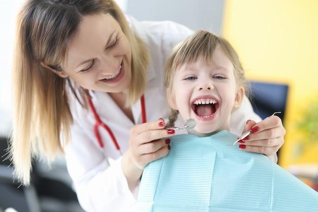 Dentista examina los dientes de la niña sonriente closeup