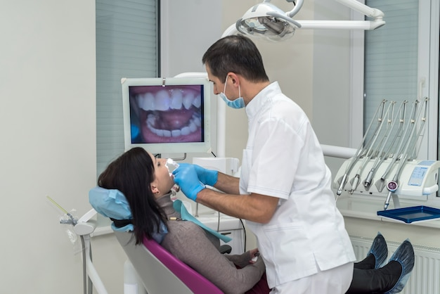 Dentista examina los dientes del paciente con cámara intraoral