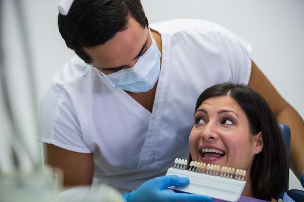Dentista examina paciente femenino con tonos de dientes