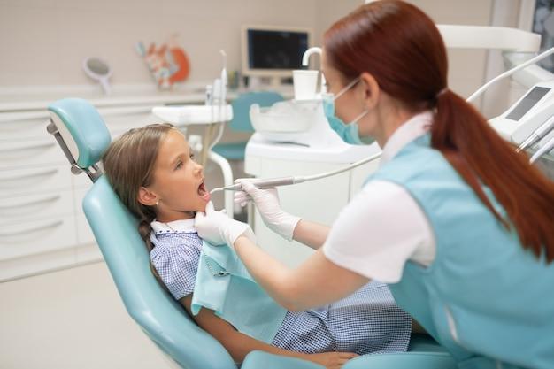 Dentista examinando. dentista pelirrojo con guantes blancos examinando colegiala en la mañana