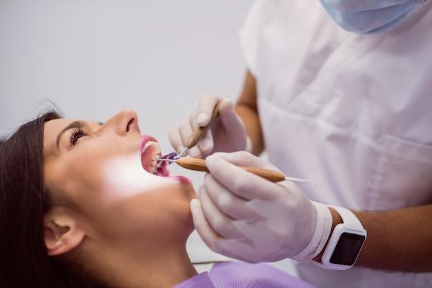 Dentista examinando los dientes del paciente femenino