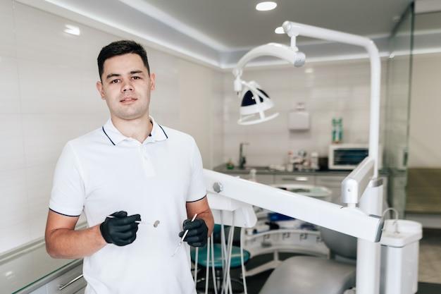 Dentista con guantes quirúrgicos posando en la oficina