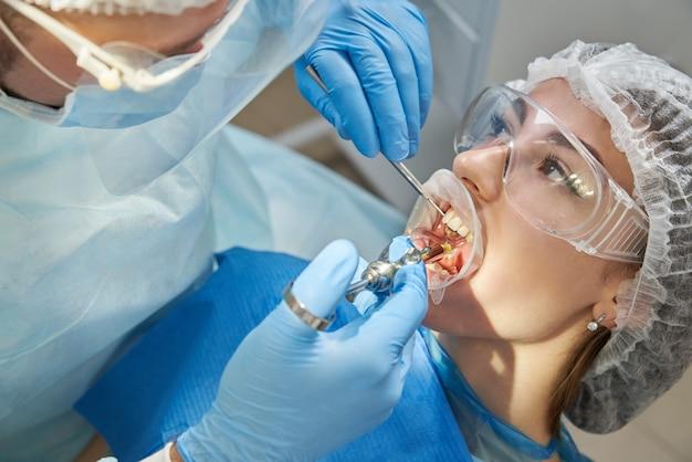 Dentista haciendo inyección de anestesia local antes de la cirugía. paciente visitando un consultorio dental