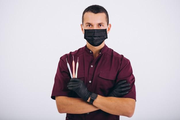 Dentista con herramientas de odontología aislado