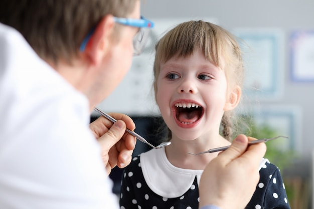 Dentista hombre mira boca abierta litle niña feliz