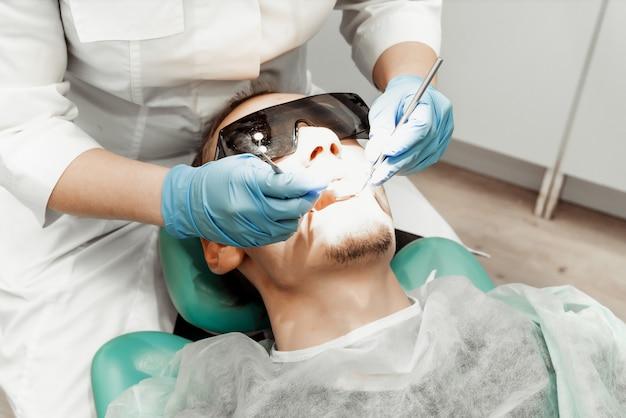 Dentista joven trata a un paciente un hombre. el médico usa guantes desechables, una máscara y un sombrero.