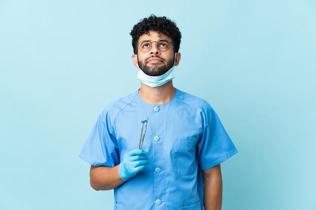 Dentista marroquí hombre sujetando herramientas aisladas