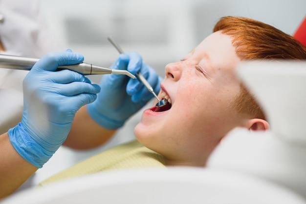 Dentista con máscara. dentista de niño pelirrojo con máscara examinando chico lindo
