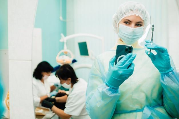 El dentista con una máscara protectora se encuentra junto al paciente y toma una foto después del trabajo.