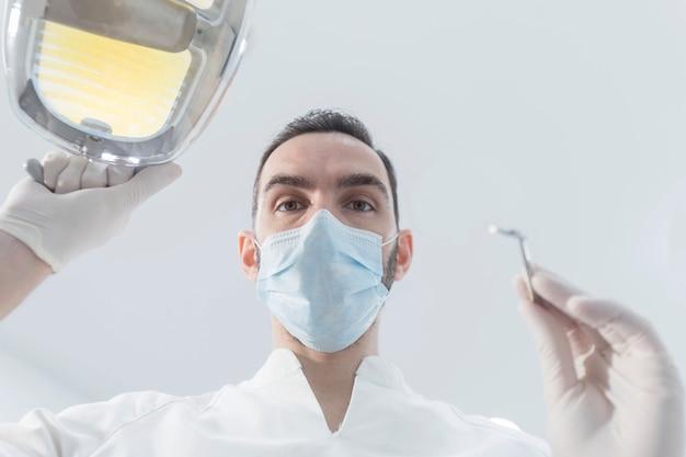 Dentista con mascarilla quirúrgica mientras sostiene el espejo en ángulo y el taladro, listo para comenzar