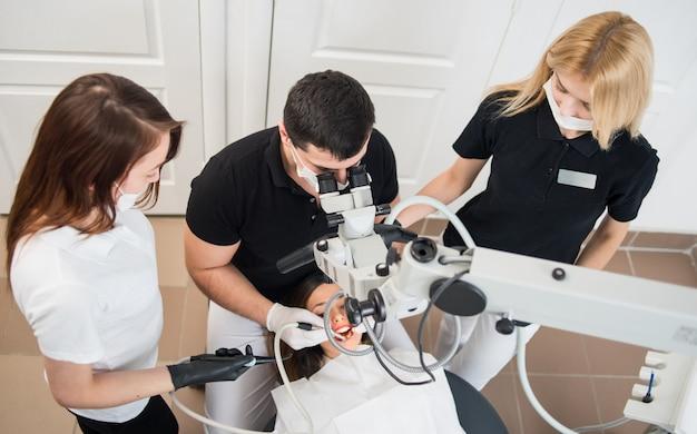Dentista masculino y dos asistentes femeninas que controlan los dientes del paciente con herramientas dentales. equipo dental