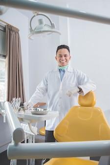 Dentista masculino con herramientas sobre clínica de consultorio médico