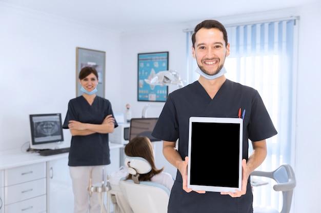 Dentista masculino sonriente que muestra la tableta digital en clínica