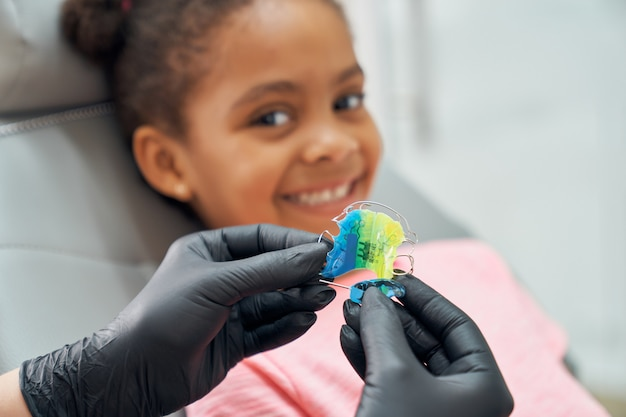 Dentista mostrando frenillos para mejorar la mordida.