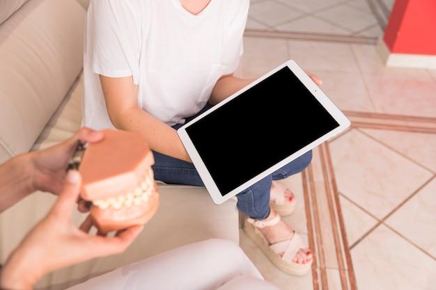 Dentista mostrando el modelo de los dientes al paciente con tableta digital