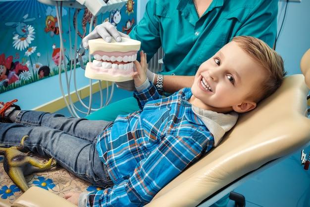 Dentista muestra una dentadura al niño