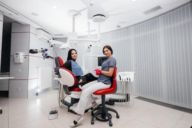 El dentista muestra una imagen de los dientes del paciente y le indica el tratamiento necesario. odontología, salud.