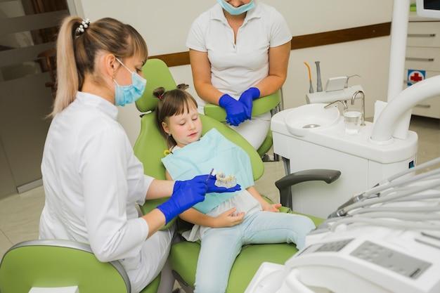Dentista y niña mirando dentaduras