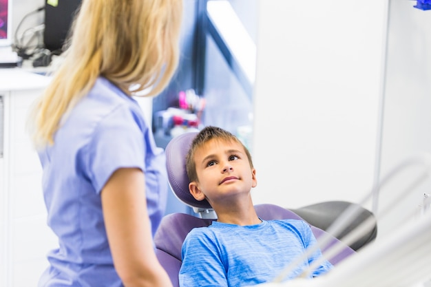 Dentista del niño que se inclina en la silla dental que mira al dentista de sexo femenino en clínica