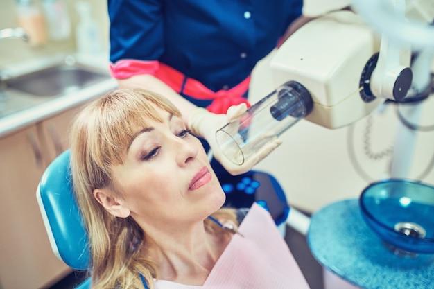 El dentista opera la unidad de rayos x intraoral dental para la imagen del diente con el paciente