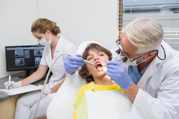 Dentista pediátrico examinando los dientes de un niño con el ayudante detrás