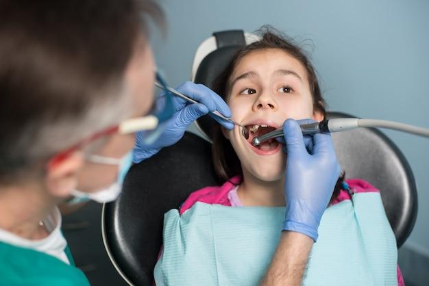 Dentista pediátrico senior que trata los dientes de una niña paciente en el consultorio dental
