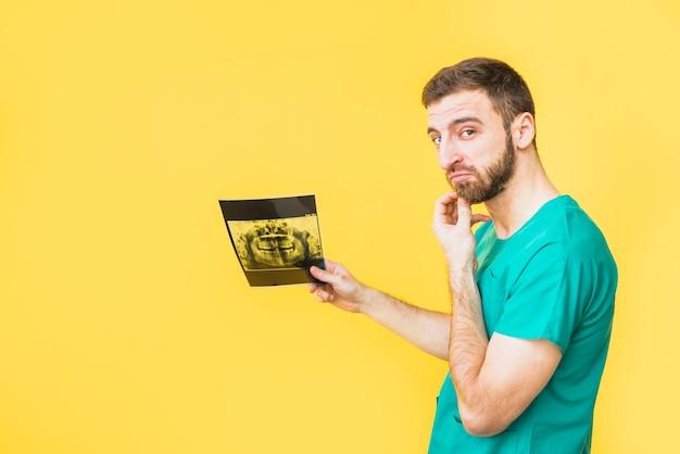Dentista pensativo que sostiene la radiografía de los dientes