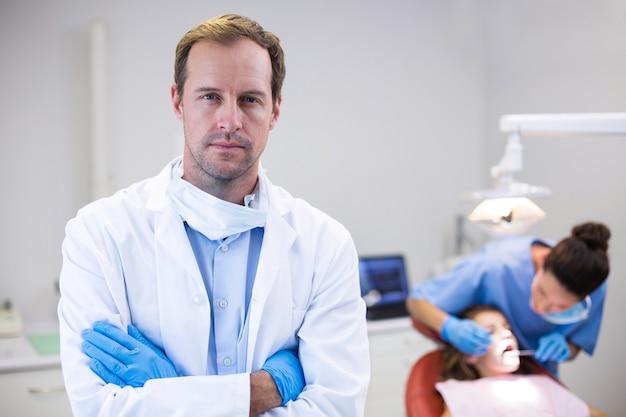 Dentista de pie con los brazos cruzados en la clínica