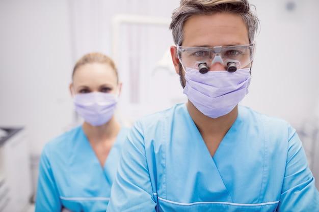 Dentista de pie en la clínica dental