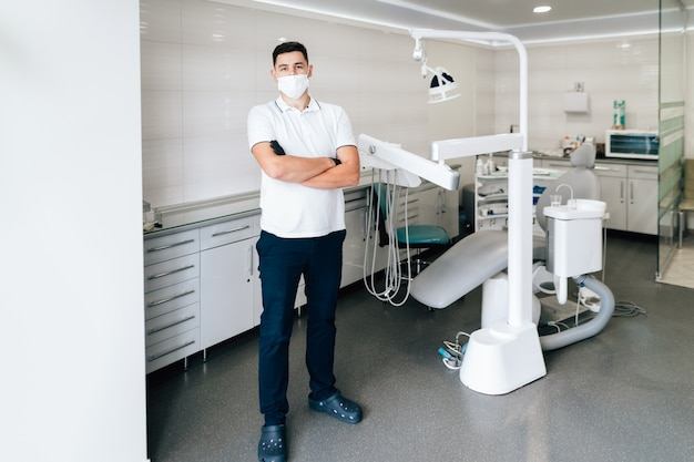 Dentista posando en el consultorio con mascarilla quirúrgica