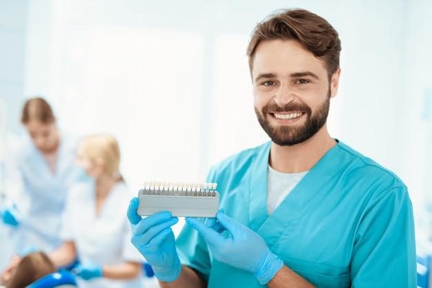 Dentista posando contra. escala de color del diente del doctor.