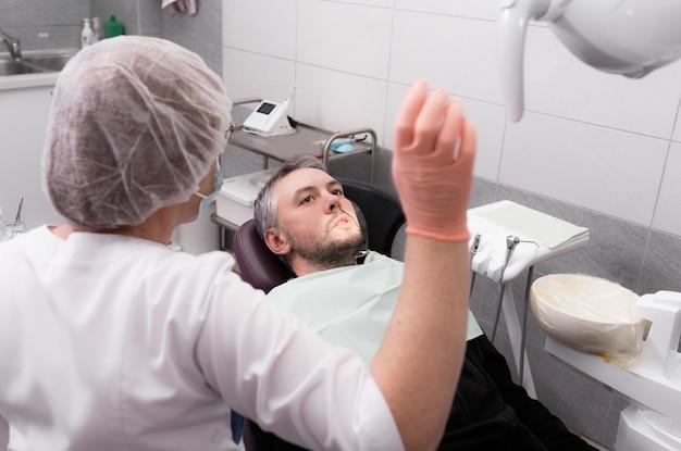 Una dentista se está preparando para examinar a un paciente masculino en el consultorio de una clínica dental