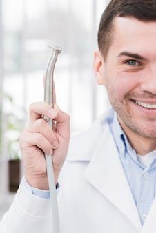 Dentista presentando herramienta