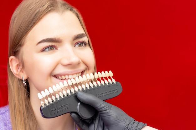 El dentista del procedimiento de blanqueamiento dental selecciona el tono inicial de la guía de colores de blanqueamiento dental de la niña