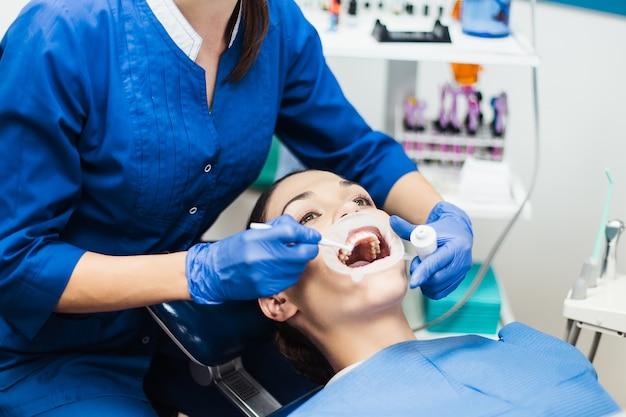 Dentista con procedimiento de blanqueamiento dental