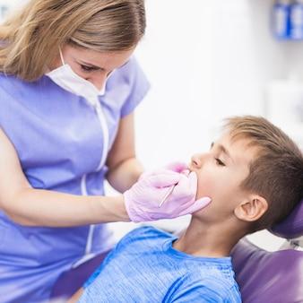 Dentista que comprueba los dientes de un muchacho en clínica