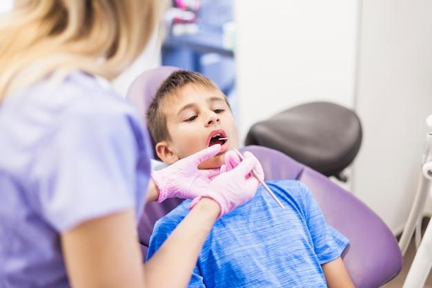 Dentista que comprueba los dientes del muchacho en clínica