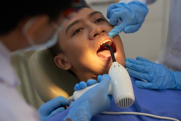 Dentista que cura el relleno del diente del paciente masculino asiático con luz ultravioleta