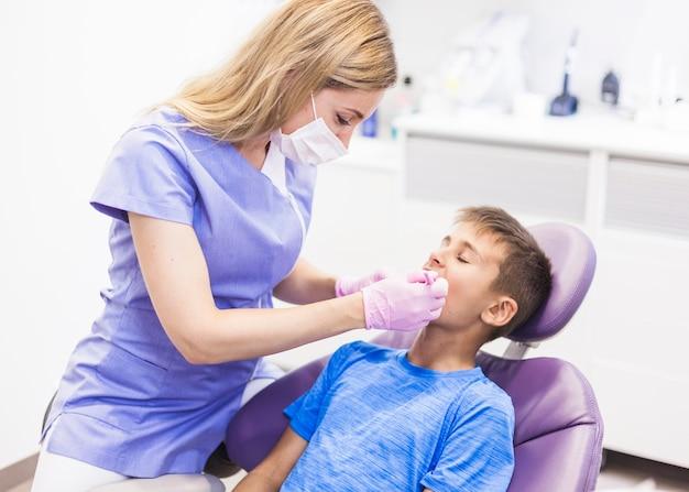 Dentista que examina los dientes del muchacho en clínica