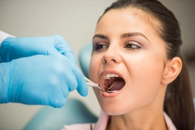 Dentista que examina los dientes de un paciente en el dentista.