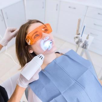 Dentista que examina los dientes del paciente con el equipo dental de la luz ultravioleta