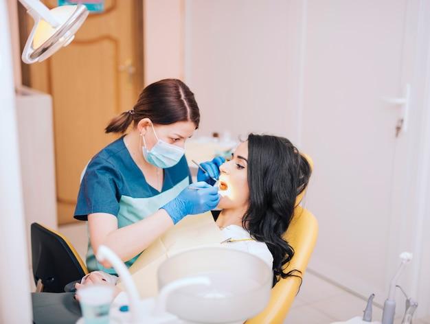 Dentista que examina los dientes de los pacientes en clínica