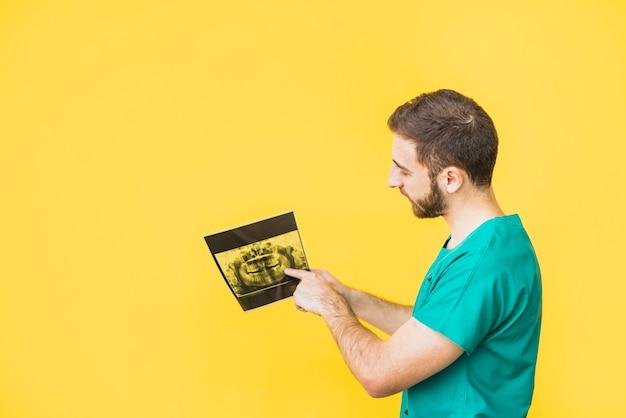 Dentista que señala el dedo a la radiografía de los dientes