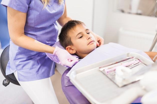 Dentista que se sienta cerca del muchacho que se inclina en silla dental en clínica