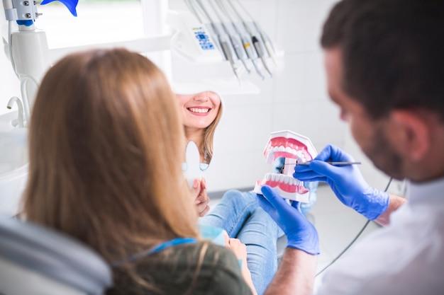Dentista que sostiene el modelo de los dientes cerca del paciente femenino que mira el espejo de mano