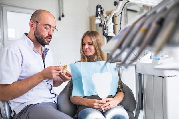 Dentista que trabaja en la mandíbula dental cerca de paciente femenino que se sienta en la silla dental