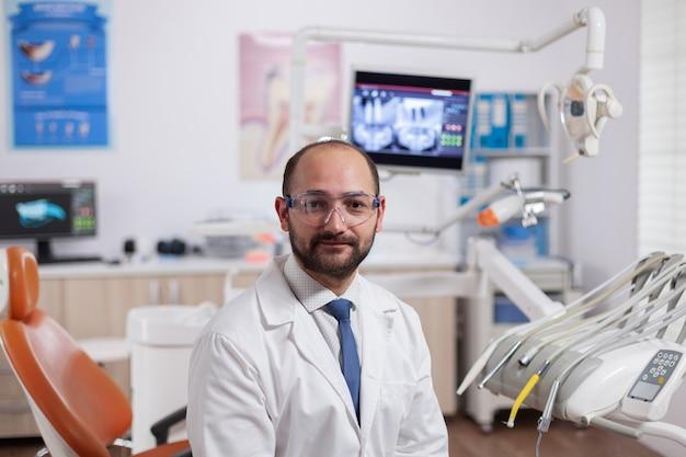 Dentista seguro en gabinete de estomatología con equipamiento naranja con uniforme dental. médico especialista en higiene bucal con bata de laboratorio mirando a la cámara en la oficina de odontología.